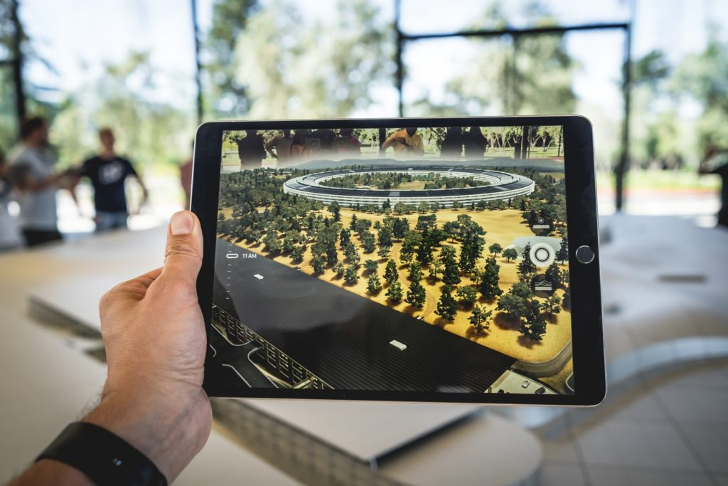person using an iPad alongside an augmented reality app.